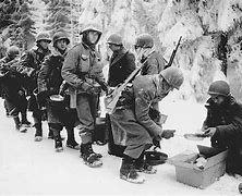 American soldiers line up for cold chow during the Battle of the Bulge in 1944.