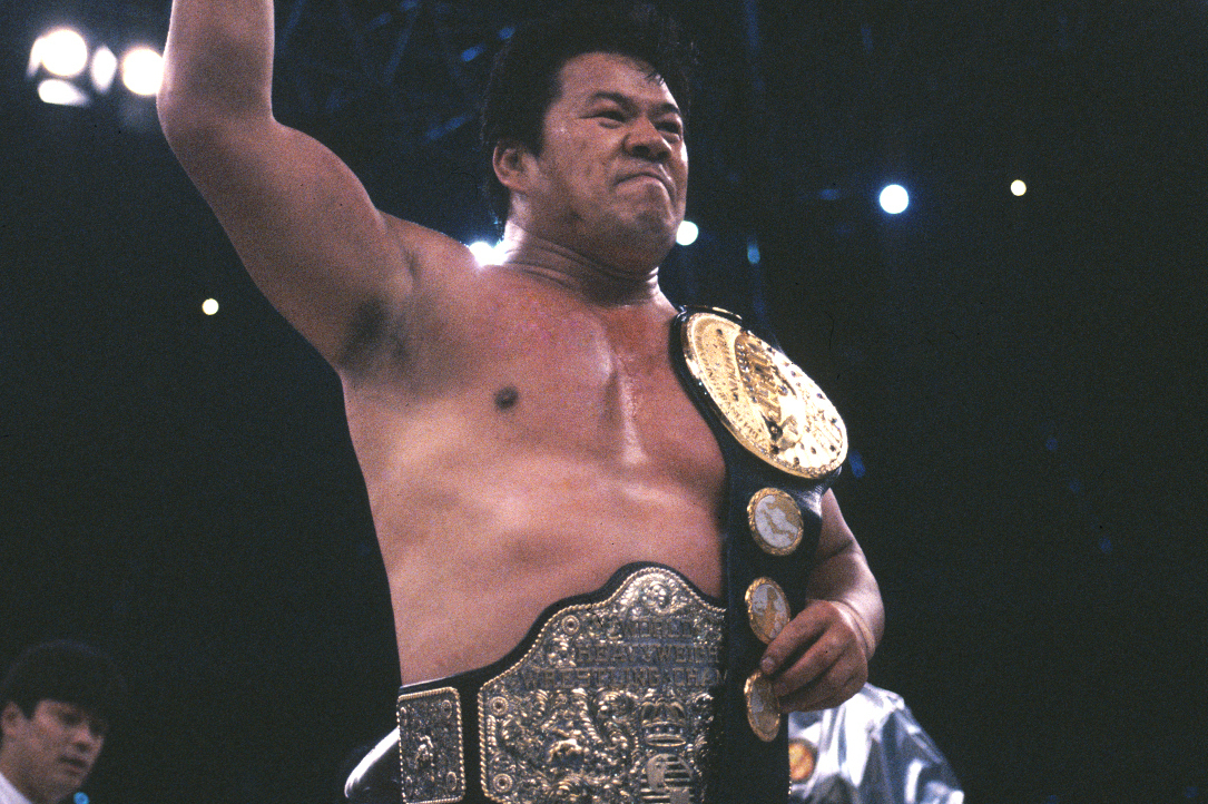 Tatsumi Fujinami with the IWGP belt on his shoulder and NWA belt around his waist.